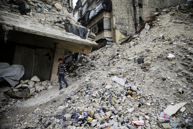 In this Monday, December 5, 2016 photo, a Syrian girl walks amid the wreckage of damaged buildings and shops in the western city of Aleppo, Syria. Aleppo shakes with explosions and gunfire day and night in both the government and rebel sides. But for supporters of President Bashar Assad at least, there is comfort in the growing sense of imminent victory in the city. A rebel defeat in Aleppo, Syria's largest city and former commercial center, is likely to reverberate across the war-torn country, where opposition forces continue to hold out in smaller, more disconnected areas. (Photo by Hassan Ammar/AP Photo)