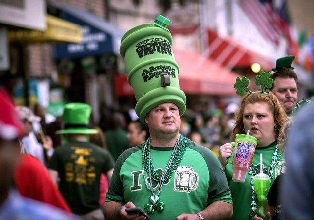 Dressed in a large foam beer keg hat Glenn Mikos of Covington, Ga. walks with his friends and family during the start of a four-day St. Patrick's Day celebration Saturday, March 14, 2015, on River Street in Savannah, Ga. (Photo by Stephen B. Morton/AP Photo)