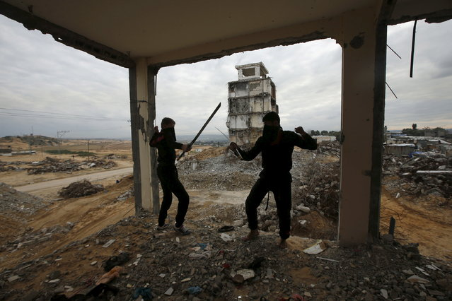 Palestinian youths fight with swords as they demonstrate their ninja-style skills for a photographer at the ruins of a building, that was destroyed in the 2014 war, in the northern Gaza Strip January 29, 2016. (Photo by Mohammed Salem/Reuters)