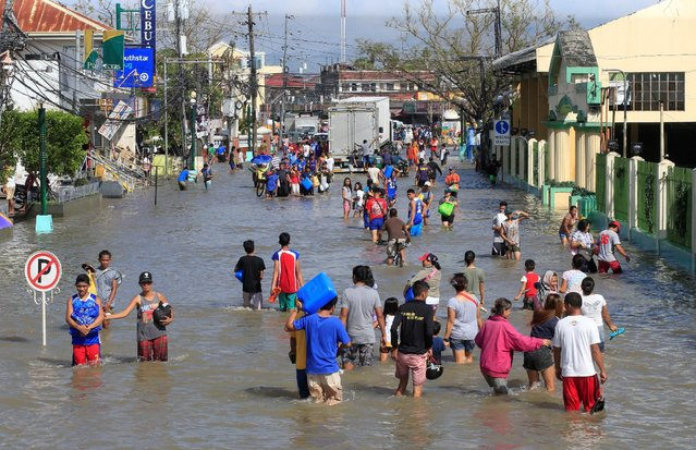 Residents wade across a flooded street brought by heavy rains and strong winds of Typhoon Nock-ten which cut through Naboa town, Camarines Sur, Bicol region, central Philippines December 27, 2016. (Photo by Romeo Ranoco/Reuters)
