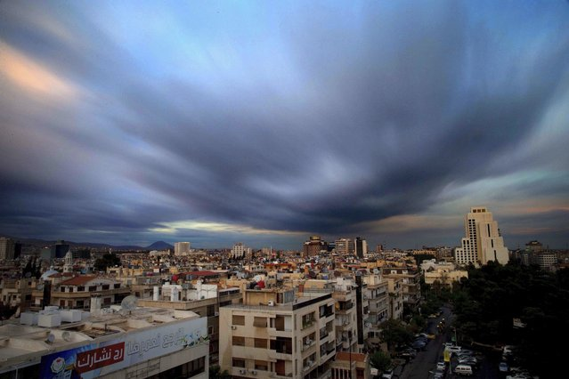 In this April 12, 2016 file picture taken with a slow shutter speed, clouds hover over the capital city of Damascus, Syria. A new Syrian law empowering the government to confiscate property is threatening to leave refugees stuck in Europe with no homes to return to. (Photo by Hassan Ammar/AP Photo)