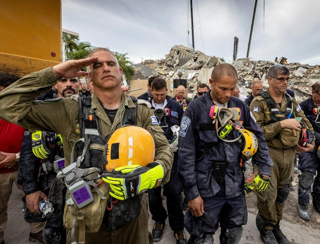 A member of the Israeli search and rescue team (left) salutes in front of the rubble that once was Champlain Towers South during a prayer ceremony and a moment of silence in Surfside, Florida, July 7, 2021. South Florida officials on Wednesday called off the search for survivors of a June condominium tower collapse, saying there was no longer any hope of pulling someone alive from the ruins of the flattened building. (Photo by Jose A. Iglesias/Pool via Reuters)