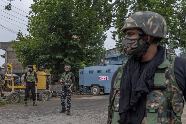 Indian paramilitary soldiers stand guard on a road leading towards the site of a gunfight in Pulwama, south of Srinagar, Indian controlled Kashmir, Wednesday, July 14, 2021. (Photo by Dar Yasin/AP Photo)