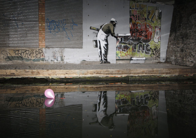 Graffiti art is seen on a wall next to the Regent's Canal, in Camden in London, December 22, 2009. British media have attributed the work to Banksy. (Photo by Luke MacGregor/Reuters)