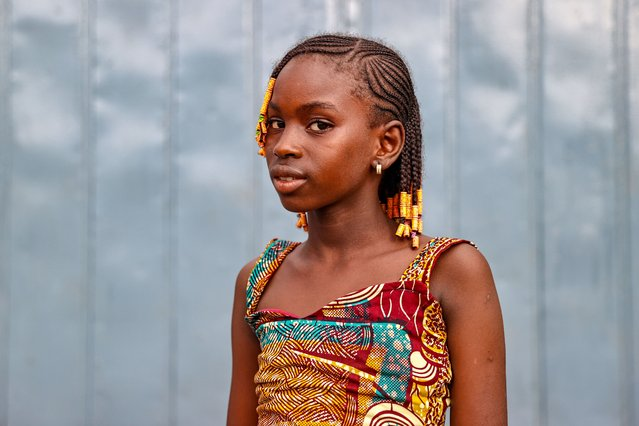 A Guinean kid poses for a photo in Conakry, Guinea on July 23, 2021. Children, most of whom start working after a certain age to support their families, have their hair braided in different ways and decorated with colorful beads on all special days, especially on holidays, despite these difficult conditions. (Photo by Ozkan Bilgin/Anadolu Agency via Getty Images)