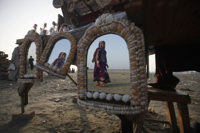 A woman is reflected in mirrors, decorated with sea shells and put up for sale, as she walks along Karachi's Clifton beach February 18, 2015. (Photo by Athar Hussain/Reuters)