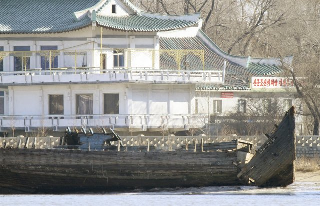 """A deserted boat is seen in front of a building, on the banks of the Yalu River, near the North Korean town of Sinuiju, opposite the Chinese border city of Dandong, January 10, 2016. The characters on the building is partially read, """"North Korea's Sun Kim Jung Un"""". (Photo by Jacky Chen/Reuters)"""