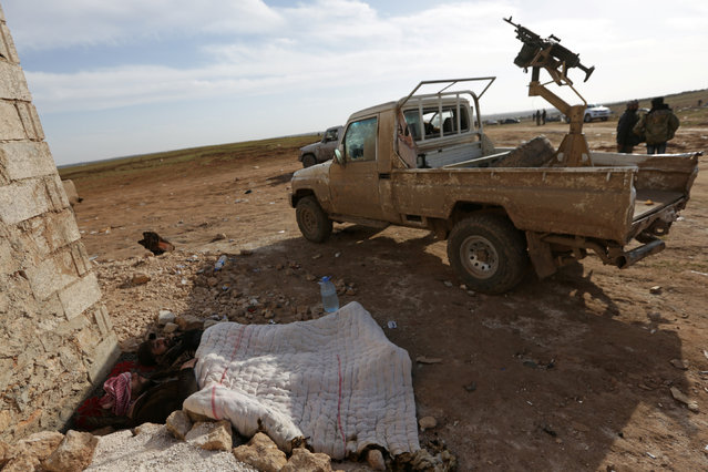 Free Syrian Army fighters rest beside a pick-up truck mounted with a weapon near Qabasin town, during an offensive against Islamic State fighters to take control of Qabasin town, near the northern Syrian town of al-Bab, Syria January 12, 2017. (Photo by Khalil Ashawi/Reuters)