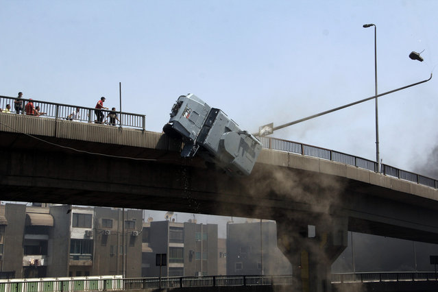 A police vehicle is pushed off of the 6th of October bridge by protesters close to the largest sit-in by supporters of ousted Islamist President Mohammed Morsi in the eastern Nasr City district of Cairo, Egypt, Wednesday, August 14, 2013. (Photo by Aly Hazzaa/AP Photo/El Shorouk Newspaper)