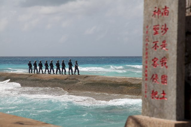 """Soldiers of China's People's Liberation Army (PLA) Navy patrol near a sign in Nansha Islands February 9, 2016. The sign reads """"Nansha is our national land,  sacred and inviolable"""". (Photo by Reuters/Stringer)"""