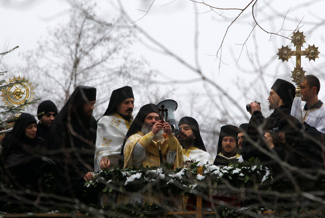 An Orthodox priest prepares to throw the cross into water during the Epiphany day celebration in Bitushe, Macedonia January 19, 2017. (Photo by Ognen Teofilovski/Reuters)
