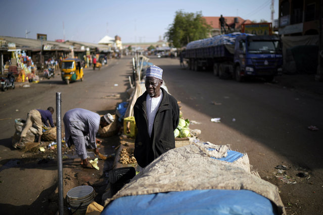 A Nigerian salesman stands in the middle of the normally busy street outside the central market in Kaduna, Nigeria, Saturday February 16, 2019. (Photo by Jerome Delay/AP Photo)