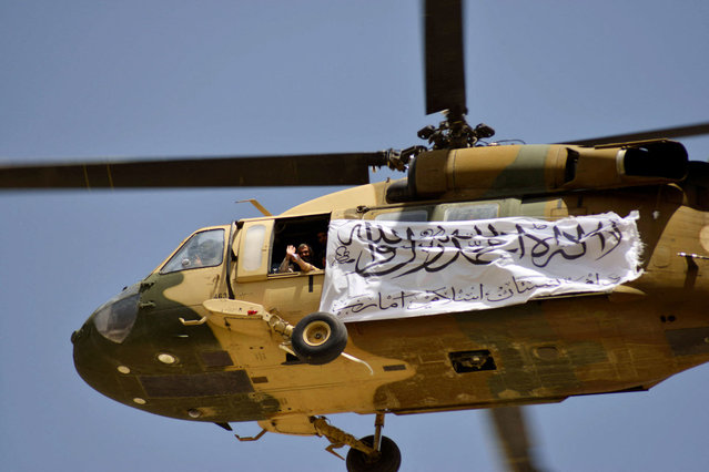 A helicopter displaying a Taliban flag flies above Taliban supporters gathered to celebrate the US withdrawal of all its troops out of Afghanistan, in Kandahar on September 1, 2021 following the Talibans military takeover of the country. (Photo by Javed Tanveer/AFP Photo)