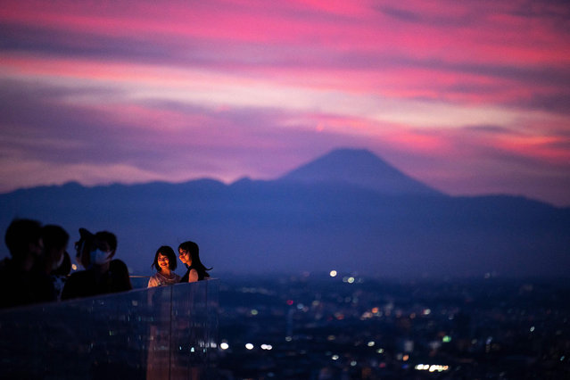 Women pose on an observatory deck with the Mount Fuji in the background, Japan's highest mountain at 3,776 meters (12,388 feet), in Tokyo on July 16, 2021. (Photo by Charly Triballeau/AFP Photo)