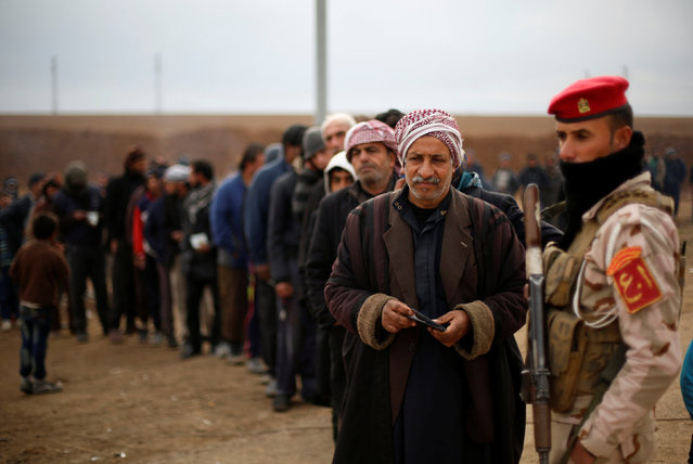 Displaced people who fled the Islamic State stronghold of the Arabi neighborhood, north of Mosul arrive to register their names at a military checkpoint before being transported to the camps in the east of Mosul, Iraq, January 25, 2017. (Photo by Muhammad Hamed/Reuters)