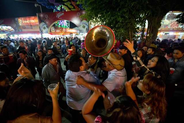 In this April 10, 2015 photo, people dance to the rhythm of a Mexican Norteño band at the Texcoco Fair on the outskirts of Mexico City. Norteño music is a music genre from Mexico's northern states, featuring brass instruments such as tubas, trumpets and drums. (Photo by Eduardo Verdugo/AP Photo)