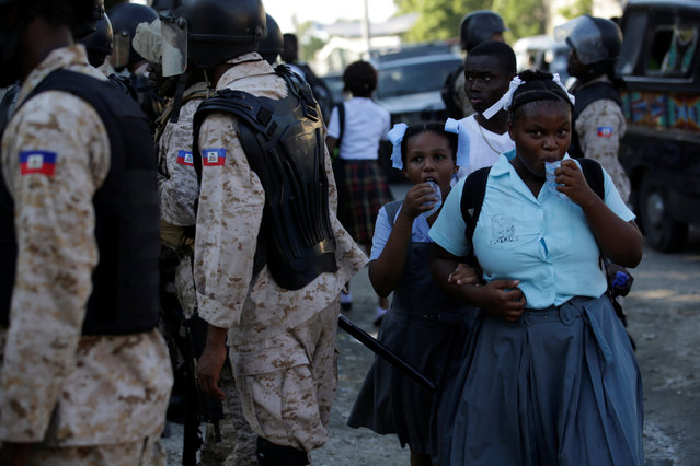 Two schoolgirls drink water from bags as they pass by a police line which is blocking a street to control a demonstration organised to protest against the results of the presidential elections, in the streets of Port-au-Prince, Haiti, December 5, 2016. (Photo by Andres Martinez Casares/Reuters)