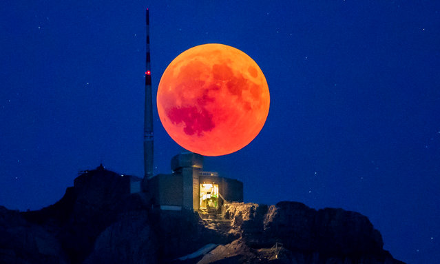 The blood moon rises behind the Saentis (2502m) Alpstein, Canton of Appenzell, Switzerland, 27 July  2018, on the night of the longest total lunar eclipse of the 21st century. (Photo by Christian Merz/EPA/EFE)