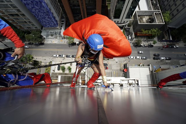 Window cleaners wearing superhero costumes greet a patient at a Children Sabará Hospital, as part of the celebration of Children's Day in Sao Paulo, Brazil on October 12, 2021. Children's Day is celebrated in Brazil on October 12. (Photo by Cris Faga/NurPhoto/Rex Features/Shutterstock)