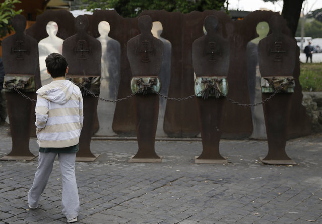 A child walks in front of a memorial dedicated to Nazi and Fascist's victims in Rome, Saturday, April 25, 2015. Italy is celebrating the 70th anniversary of a partisan uprising against the Nazis and their Fascist allies at the end of World War II. The anniversary marks the day in 1945 when the Italian resistance movement proclaimed an insurgency as the Allies were pushing German forces out of the peninsula. (Photo by Gregorio Borgia/AP Photo)