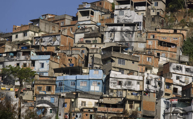 "Giant photographs of women, part of the ""Women Are Heroes"" cover the walls of homes in the favela Providencia in Rio de Janeiro, Brazil August 25, 2008. The project depicts women whose relatives were the victims of clashes between police and drug traffickers. (Photo by Bruno Domingos/Reuters)"
