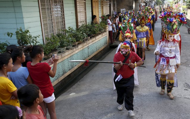 """A penitent locally called """"Morions"""" teases a resident as they parade during the start of Holy Week celebrations in Mogpog, Marinduque in central Philippines March 21, 2016. (Photo by Erik De Castro/Reuters)"""