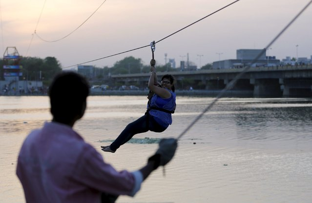 A woman rides a zip-line across the Sabarmati river on a hot summer evening in Ahmedabad, India, May 10, 2015. The length of the zip-line is around 350 metres, a municipal official said. (Photo by Amit Dave/Reuters)