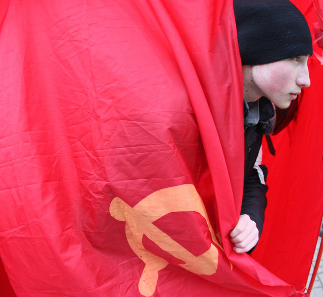 """A young activist wraps himself in a Soviet-era communist flag as pro-Russian activists from the so called """"Eastern Front"""" movement take part in a rally in front of the Lenin monument in the center of the industrial Ukrainian city of Donetsk on February 26, 2014. Ukraine's pro-Western interim leaders were set to unveil their new cabinet today after disbanding the feared riot police as they sought to build confidence in the splintered and economically ravaged ex-Soviet nation. (Photo by Alexander Khudoteply/AFP Photo)"""