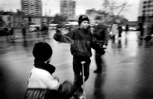 Sasha, 16, breaks the everyday monotony of begging and getting high to enjoy a few minutes on a borrowed scooter as Denise encourages him, 2002. The punishment for these children who get caught stealing varies from beatings and arrest, to having the sewers set alight where they become unsuitable for the children to sleep in during the harsh winters. (Photo by Kurt Vinion /Getty Images)