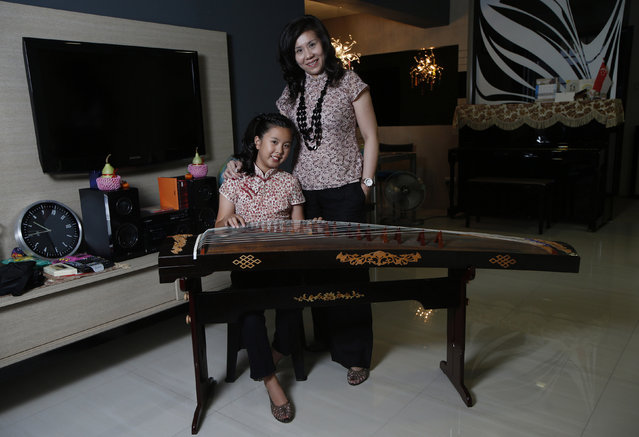 Samann Loh, 40, and her daughter Given Tan, 10, pose for a photograph in their apartment in Singapore February 25, 2014. Samann works as a human resource director at a preschool education group. As a child she had many ambitions, including being a fashion designer and an air stewardess. She later realised her dream of becoming an air stewardess. Samann hopes her daughter can pursue something that she is truly passionate about. Given Tan would like to be a fashion designer when she is older. (Photo by Edgar Su/Reuters)