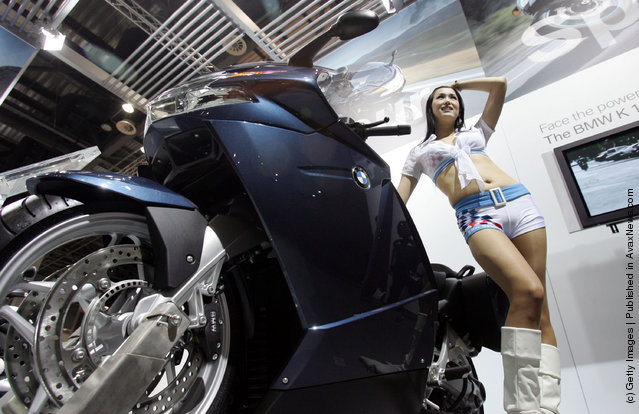 A Model poses next to a BMW motorcycle K 1200 GT