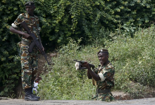 A soldier points his rifle at protesters after he fires warning shots during a protest against Burundi President Pierre Nkurunziza and his bid for a third term in Bujumbura, Burundi, May 21, 2015. (Photo by Goran Tomasevic/Reuters)
