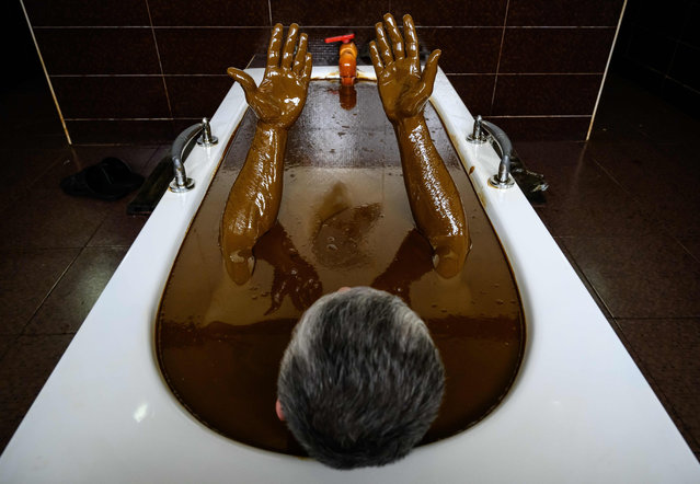 A man bathes in a tub filled with Naftalan crude oil during a treatment session at Sehirli Naftalan Health Center, some 300 kilometres (186 miles) from capital Baku, on March 21, 2019. Immersed up to her neck in crude oil, a Russian woman suffering from joint disease smiles in delight, confident that the treatment at a spa in northwestern Azerbaijan will cure her painful condition. (Photo by Mladen Antonov/AFP Photo)
