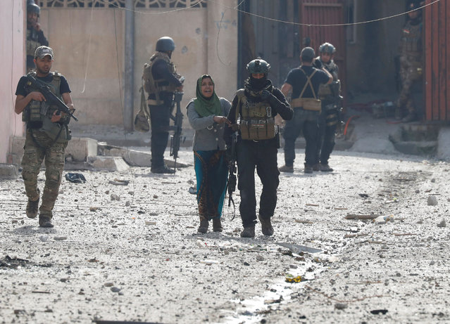 A woman walks with an Iraqi special forces soldier after she crossed from Islamic State controlled part of Mosul to Iraqi troops controlled part of Mosul, Iraq March 1, 2017. (Photo by Goran Tomasevic/Reuters)