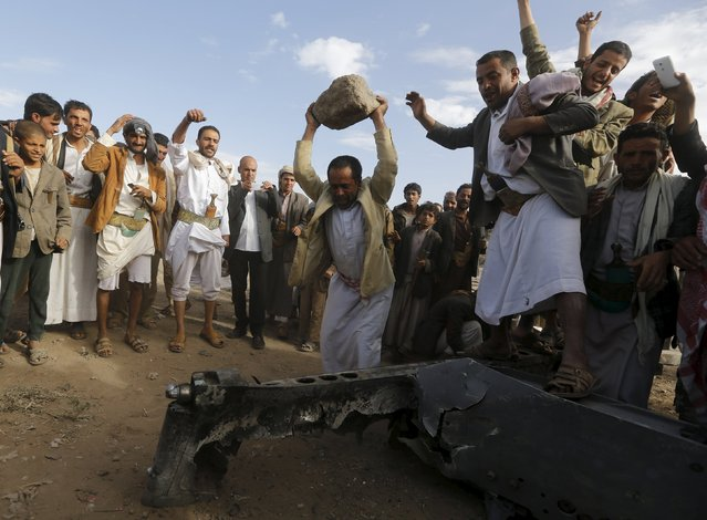 People destroy part of a Saudi fighter jet found in Bani Harith district north of Yemen's capital Sanaa May 24, 2015. (Photo by Khaled Abdullah/Reuters)