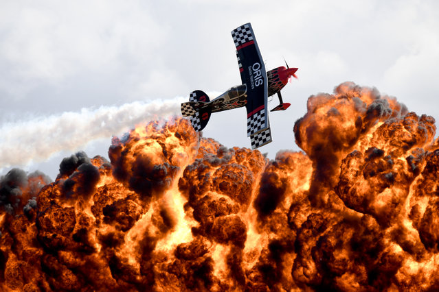 A member of the Tinstix of Dynamite aerobatics team flies in front of a wall of fire during the Australian International Airshow in Melbourne on March 5, 2017. The annual event sees 180,000 visitors over the 3-day public event held at the Avalon Airfield some 80kms south-west of Melbourne. (Photo by Mal Fairclough/AFP Photo)