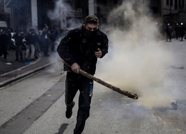 A protestor runs to avoid teargas as riot police look on during a protest by Greek farmers against higher taxes outside the Agriculture ministry in Athens, on March 8, 2017. Greek farmers protesting higher taxes clashed with riot police firing tear gas in Athens, an AFP journalist said. Two people were detained after the windows of two police vans were smashed, a police source told AFP. (Photo by Angelos Tzortzinis/AFP Photo)