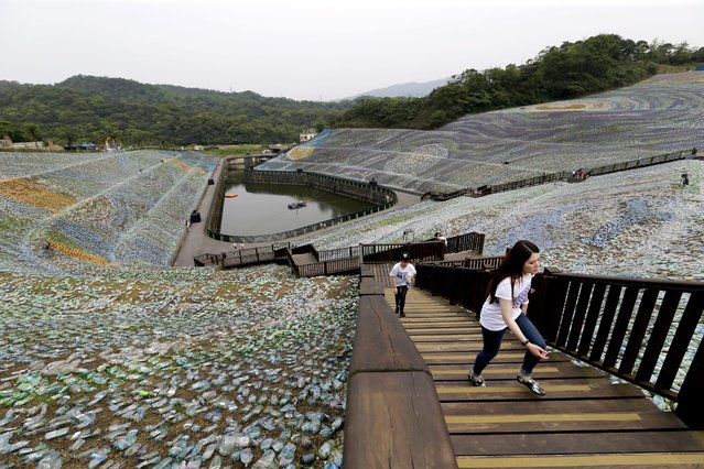 "People walk around ""The Starry Paradise"", a recreation of Van Gogh's painting ""The Starry Night"" made from discarded plastic bottles at the Embrace Cultural and Creative Park in Keelung, Northern Taiwan, 21 April 2016. The recreated Van Gogh painting is made from four million discarded plastic bottles that covers 53 hectares of the park. The installation cost 90 million Taiwan dollars (2.5 Million Euro) that aims to promote environmental protection. (Photo by Ritchie B. Tongo/EPA)"