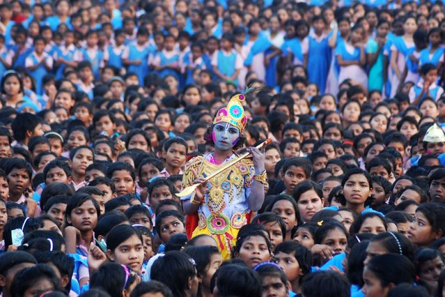 An Indian schoolchild dressed as the Hindu god Krishna and adorned with coloured powder stands among other students during celebrations for the spring festival Holi in Bhubaneswar on March 16, 2014. Holi, the popular Hindu spring festival of colours is observed in India at the end of the winter season on the last full moon of the lunar month. (Photo by Asit Kumar/AFP Photo)