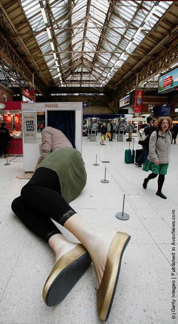 Sculpture of a giant lady with her head stuck in a photo booth