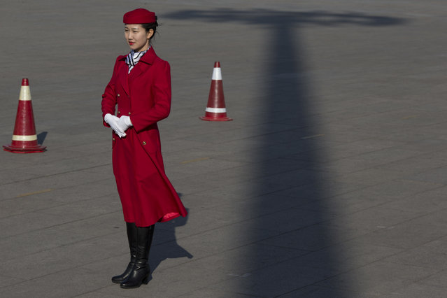 In this photo taken Wednesday, March 8, 2017, a hospitality staff member pose for photos near the shadow of a tall light pole near the Great Hall of the People where a plenary session of the National People's Congress is held in Beijing, China. (Photo by Ng Han Guan/AP Photo)