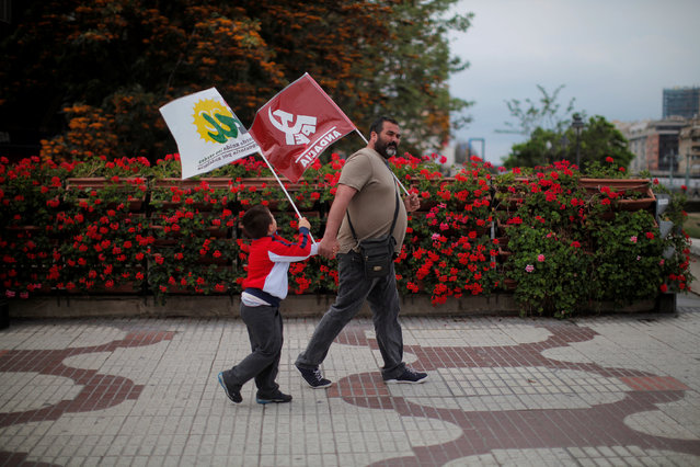 A man and his son carry flags of the Communist party and Izquierda Unida (IU) as they leave a May Day rally in Malaga, Spain, May 1, 2016. (Photo by Jon Nazca/Reuters)