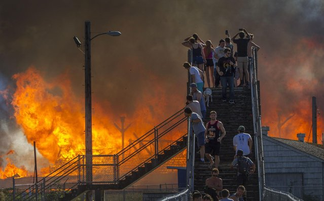 Onlookers watch the Civic Stadium burn in Eugene, Ore., Monday, June 29, 2015. (Photo by Andy Nelson/The Register-Guard via AP Photo)