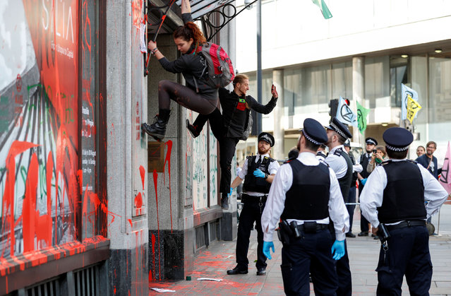 Police officers observe as activists climb down from the awning over the Brazilian Embassy's entrance during Extinction Rebellion climate change protest in London, Britain, August 13, 2019. (Photo by Peter Nicholls/Reuters)