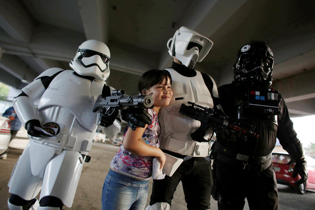 Members of the Star Wars fan club, dressed as a Stormtrooper (L), Scout Trooper (C) and Imperial Tie Pilot pose for a picture with a girl outside a hospital's emergency ward during Star Wars Day celebrations in Monterrey, Mexico May 4, 2016. (Photo by Daniel Becerril/Reuters)