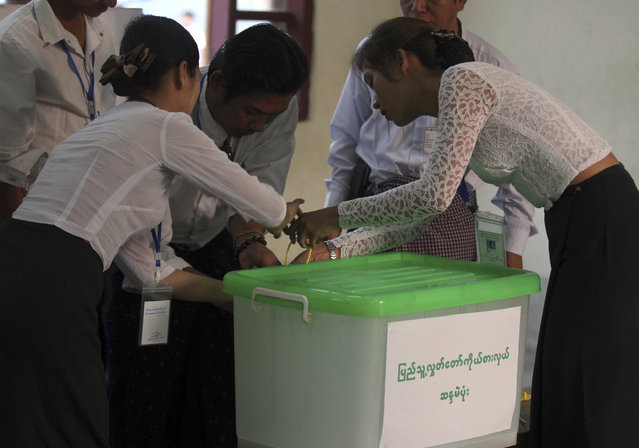 Officials of the Union Election Commission seal an empty box as they prepare to open a polling station on the outskirts of Yangon, Myanmar, Saturday, April 1, 2017. By-election began Saturday for 19 vacant parliament seats. (Photo by Thein Zaw/AP Photo)