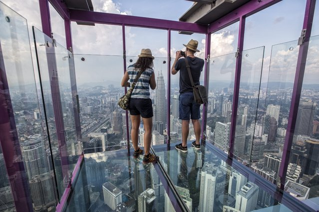 Tourists take a panoramic view of Kuala Lumpur from a skybox during a media preview at Kuala Lumpur Tower in Kuala Lumpur, Malaysia, 05 May 2016. Skybox, 421 metres above ground level will be the latest tourists attraction at Kuala Lumpur Tower, the 7th tallest freestanding tower in the world. (Photo by Ahmad Yusni/EPA)