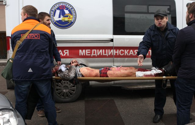 Men carry an injured person on a stretcher outside Technological Institute metro station in Saint Petersburg on April 3, 2017. (Photo by Alexander Tarasenkov/AFP Photo)