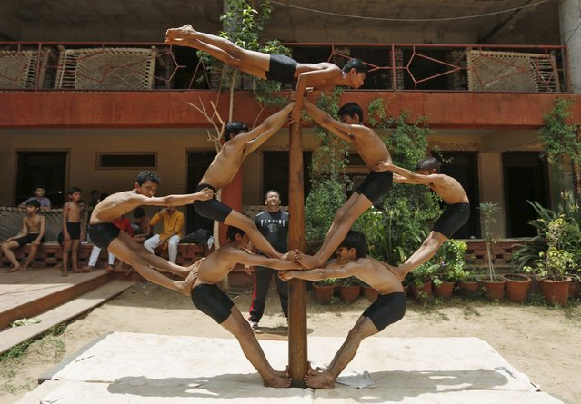 "Boys practice ""Malkhamb"" (traditional Indian gymnastics) during a rehearsal for the upcoming annual Rath Yatra, or chariot procession, in Ahmedabad, India, July 5, 2015. Hindu devotee perform various stunts including Malkhamb as part of the annual Rath Yatra celebrations which commemorates a journey by Hindu god Jagannath, his brother Balabhadra and sister Subhadra, in specially made chariots. The annual Rath Yatra is celebrated on July 18. (Photo by Amit Dave/Reuters)"
