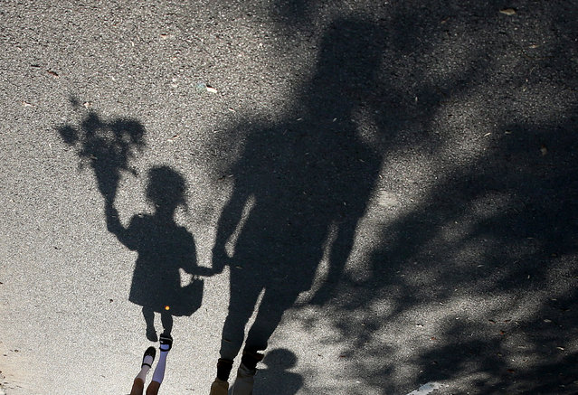 A 180 degrees rotated photograph shows the shadows of Polina (L), a six-year-old Belarusian first grade school girl, and her father, cast on the street while on their way to Polina's first day of school, which marks the traditional start of the academic year, in Minsk, Belarus, 02 September 2019. The start of a new academic year in Belarus, officially called Day of Knowledge, is a festive day for all school and university students in the country. (Photo by Tatyana Zenkovich/EPA/EFE)